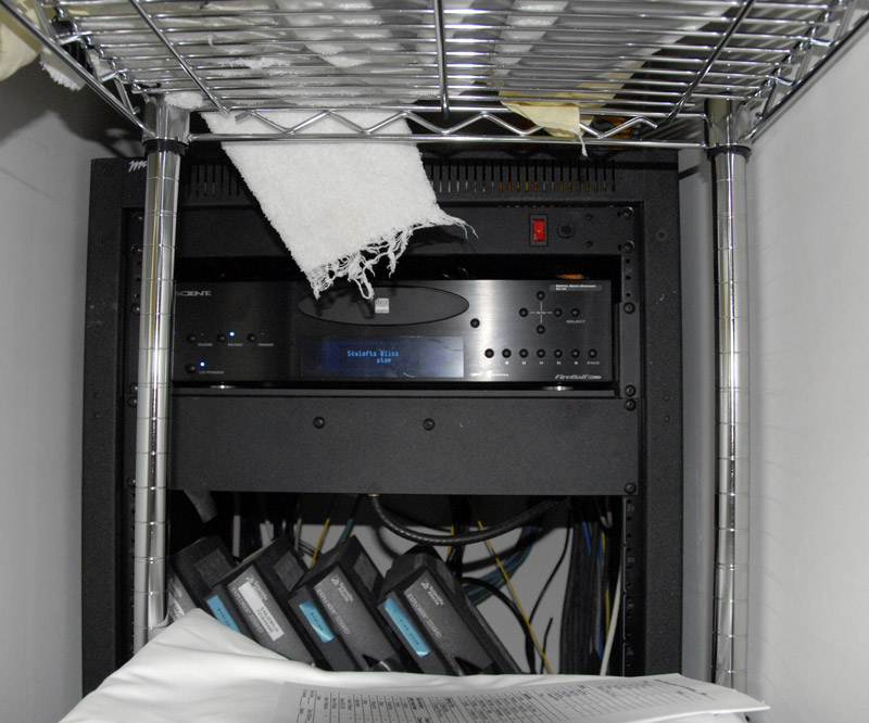 A locked closet containing housekeeping supplies and a rack of high-tech equipment is found in each loft at SkyLofts.  I arrived one day to discover the closet open.  Being the geek that I am, I had to snap a few photos.  In this shot you can see a Fireball Escient music server and no less than four Scientific Atlanta high-definition cable boxes, powering the many flat-panel TV's throughout the loft.  The rack also included a 24-port networking switch, WiFi base station, a Crestron control processor, and other miscellaneous gear.  Cool stuff.